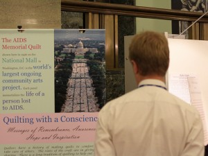 A visitor looking at one of the four panels explaining American Quilting Traditions made for the exhibit