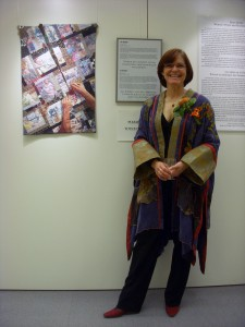 "Fiber Artist Lea McComas in front of her quilt ""The Mending"""