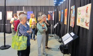 Visitors spending time with the wWomen, Peace and Security  Challenge Quilts.