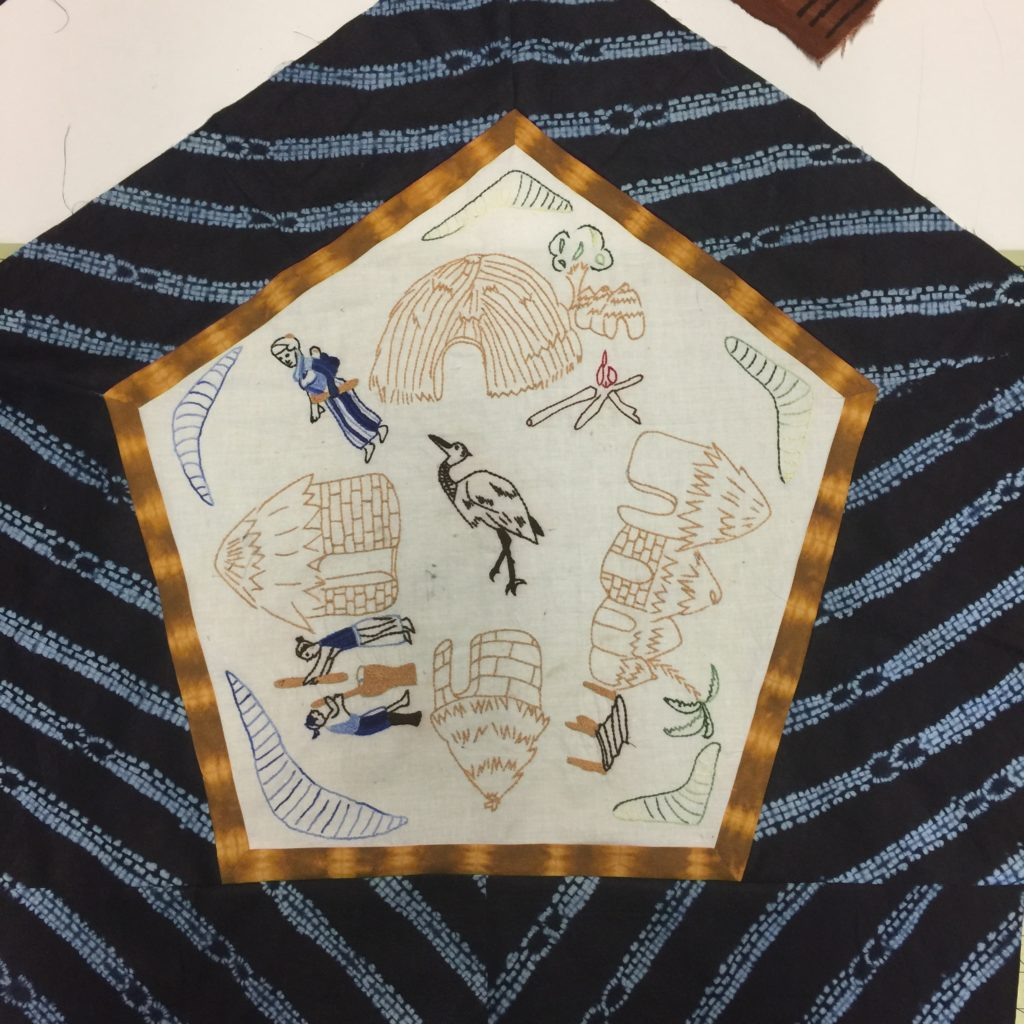 Embroidered village life block surrounded by gold and blue fabric borders