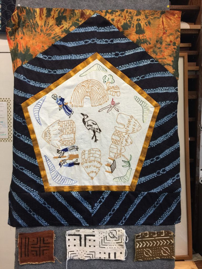 Embroidered village scene from Mali with indigo border and bologlan fabric